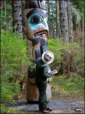 Ranger looking at one of the totem poles at Sitka National Historical Park