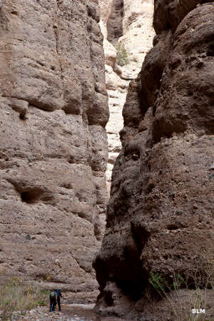 Hikers at the entry to a slot canyon in Aravaipa Canyon Wilderness