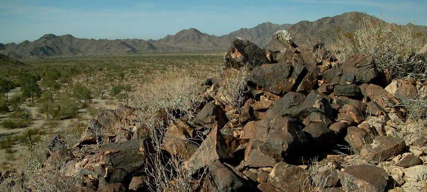 Looking past a jumble of basalt rocks to the North Maricopa Mountains