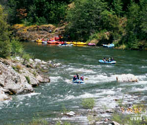 People in inflatable rafts floating down the Salmon River