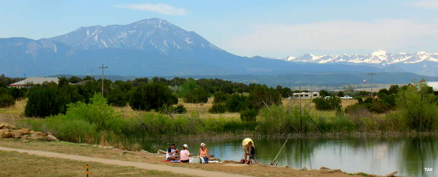 A view of fishermen setting up their equipkment beside a lake with the Spanish Peaks rising in the background