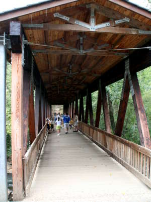 A covered foot bridge across the Chattahoochee River near Roswell Mill