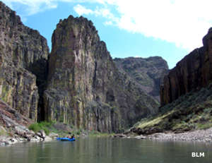 Looking upstream on Deep Creek, past a boat into the deeply carved basalt canyon