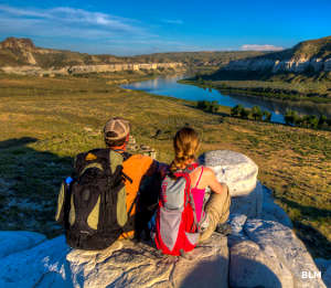 View of a couple with backpacks sitting on a rock beside the Missouri River