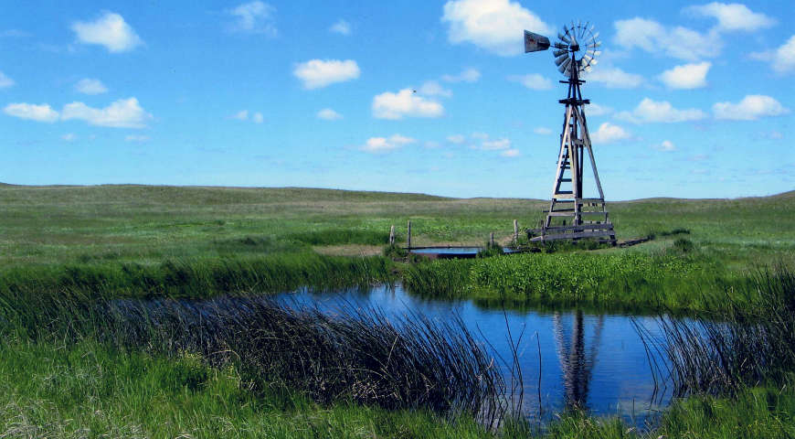 A windmill above a pond along the Sandhills Journey
