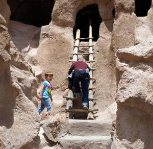 Climbing a ladder at Bandelier National Monument
