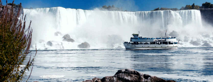 A view of the Maid of the Mist tour boat sailing below Niagara Falls