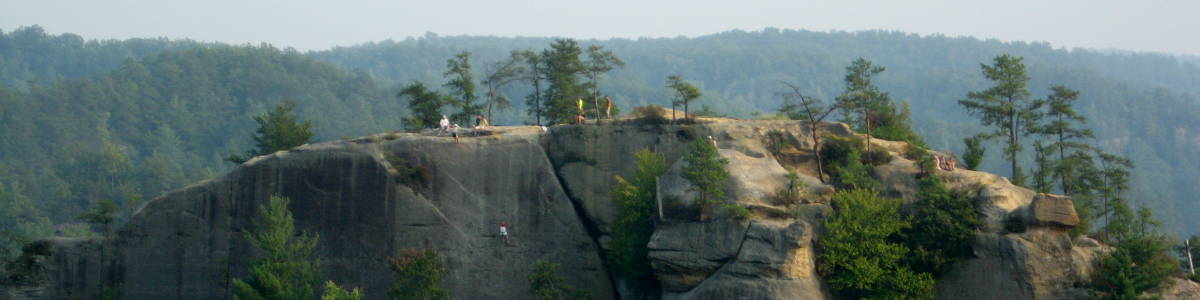 Kentucky: Folks scaling a vertical rock wall in Clifty Wilderness