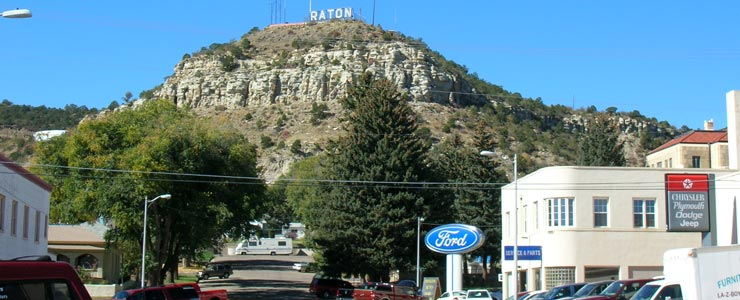 The Raton sign rises above the city