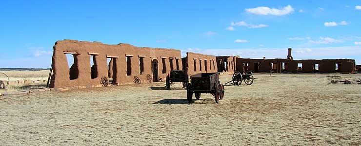 Freight wagons and a cannon stands in front of adobe walls at Fort Union National Monument