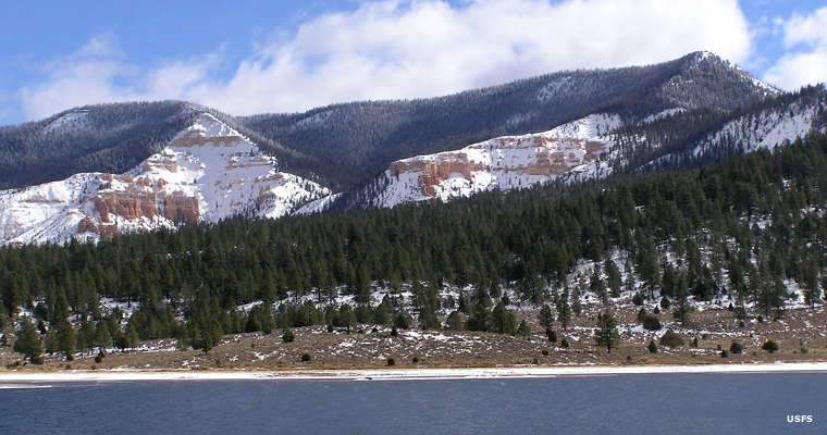 Looking across Pine Lake into snow-covered hills in Dixie National Forest