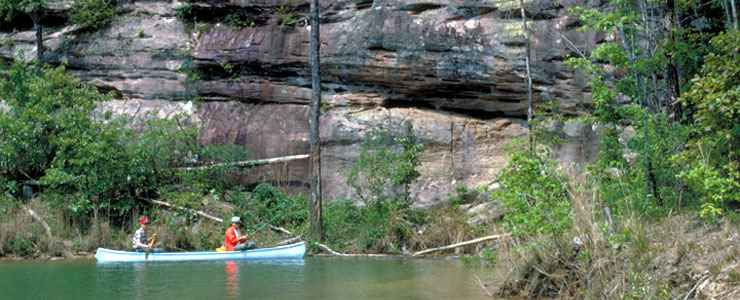 Fishermen in a canoe near a limestone bluff on the Sipsey Fork of the West Fork River