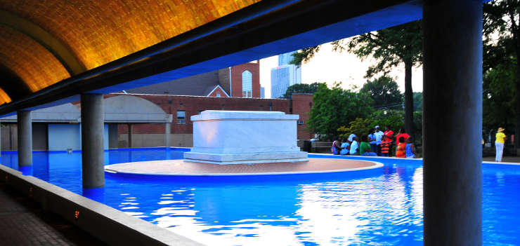 A mausoleum on a concrete pedestal surrounded by a pool of water at The Martin Luther King Jr. Memorial