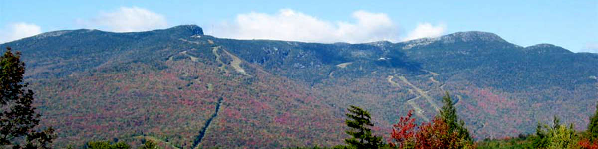 Looking at Mount Mansfield from a distance, forested, ski slopes and some autumn colors