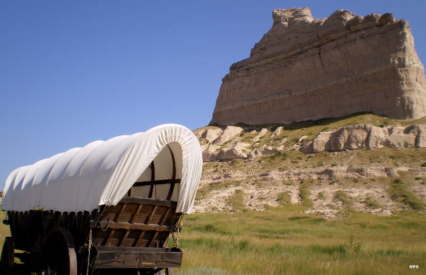 A covered wagon on the grassland below Scotts Bluff