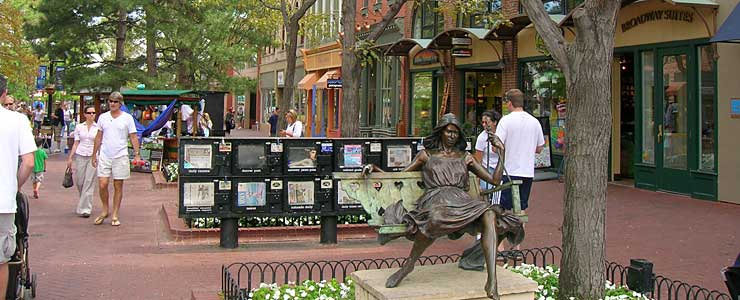 Bronze sculpture of a woman with flowing hair and a flowing dress sitting on a park bench on the Pearl Street Mall in Boulder